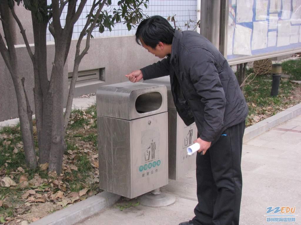 校园/青年教师用手擦洗垃圾箱