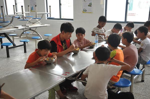 6志愿者们和孩子们一起在食堂就餐