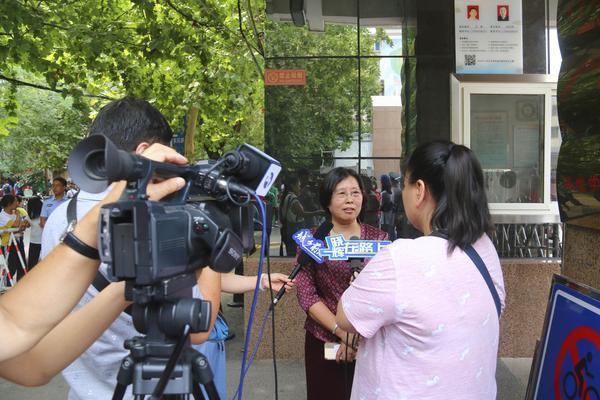 5贾惠芬校长在校门口接受新闻媒体采访