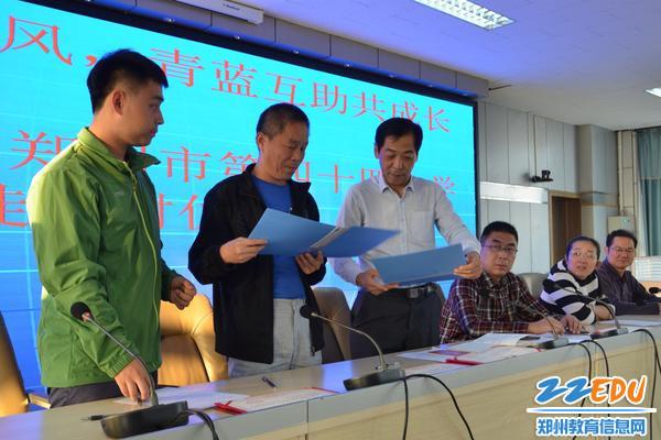 在张松晨校长(右1)指导下进行师徒代表签结对协议