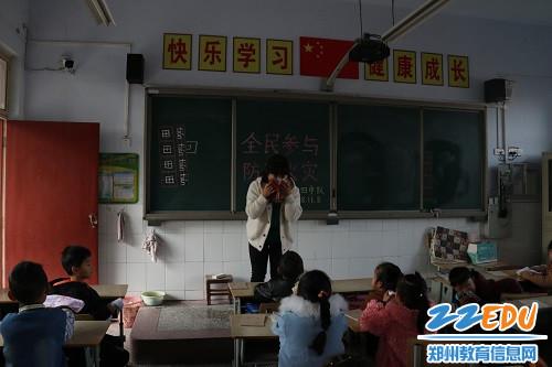 老师向学生讲解湿毛巾捂住口鼻的正确姿势
