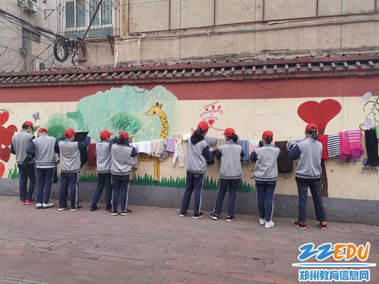 5、志愿者把衣服分类整理并把悬挂在爱心墙上