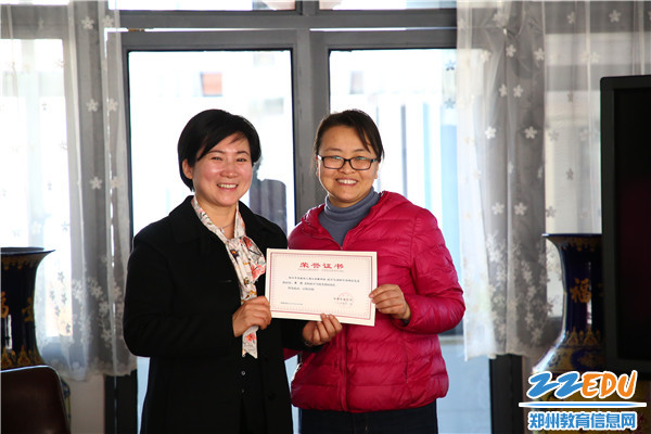 市实验幼儿园园长郝江玉为市优秀教研组长李筠老师颁发证书
