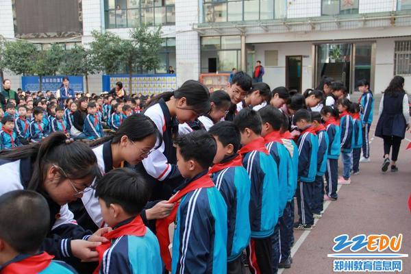 扶轮外国语学校团员为少先队员们佩戴红领巾