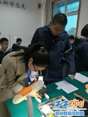 4生物老师认真观看显微镜下学生的实验结果