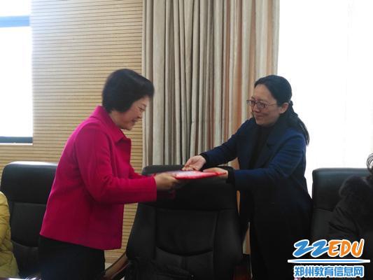薛莹校长(右)为退休教师颁发光荣退休证书