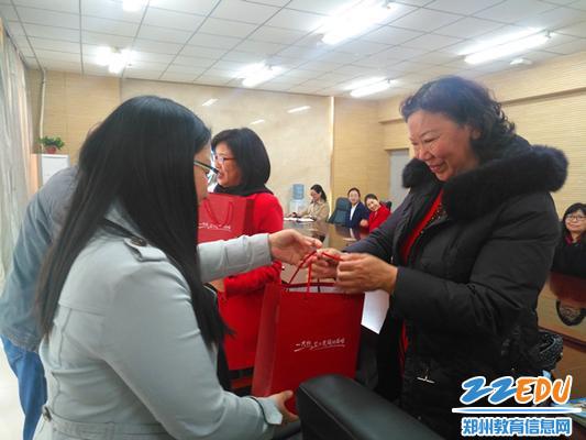 校工会主席谭春红为退休教师颁发纪念品