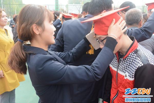 班主任老师为学生佩戴成人帽
