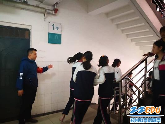 导护教师引导学生下楼疏散
