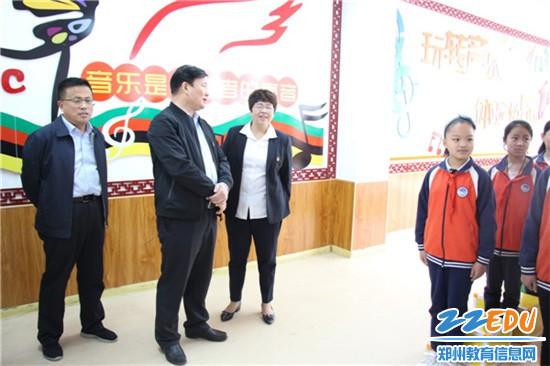 郑州市教育局局长王中立向平安路学校校长郭爱霞了解社团建设情况