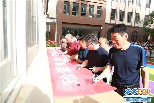 家长们在预防溺水的横幅上亲笔签上自己的名字