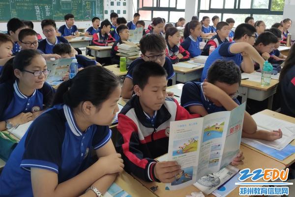 06  学生在认真观看《郑州市中小学生防汛知识》宣传册