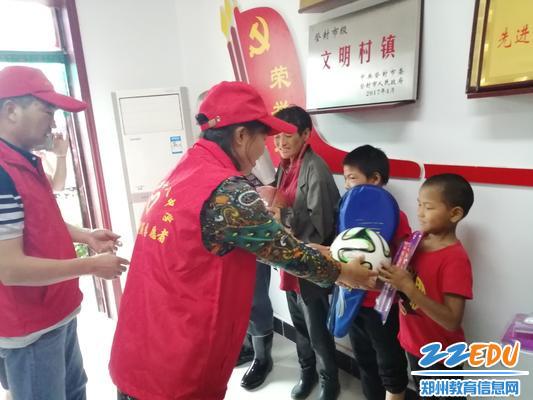 党员志愿者杨红革为贫困儿童送足球