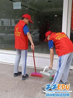 学生志愿者清扫地上的烟头垃圾