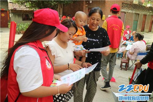 志愿者给社区群众发放并讲解垃圾分类宣传页