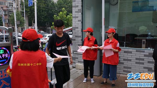 志愿者为学生发放报到流程图