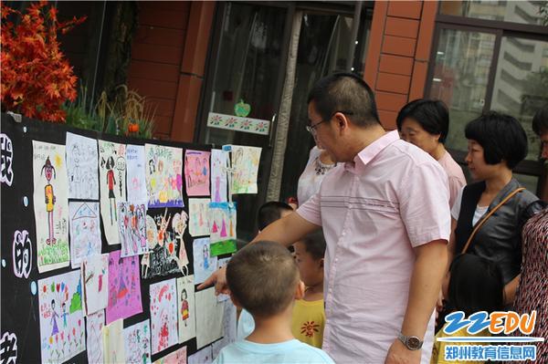8.1家长和孩子们驻足欣赏宝贝们对老师的画像