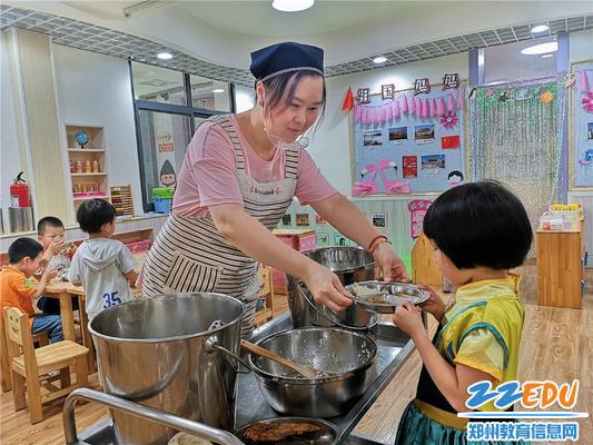 2午餐时间,丁丽丽老师给孩子盛饭