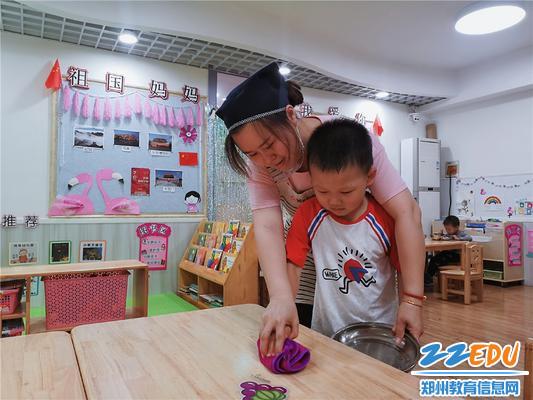 3丁丽丽老师在教孩子擦桌子,帮助他们养成良好的卫生习惯