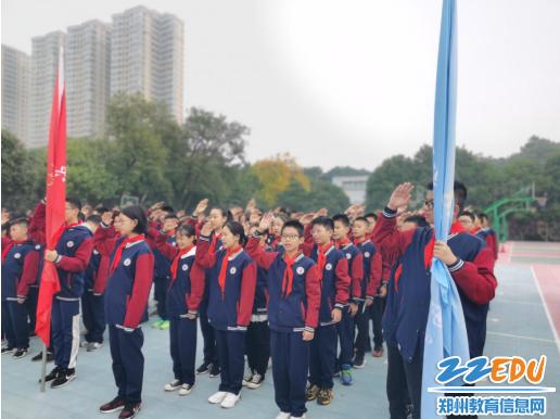 七年级全体少先队员面对国旗庄严立正行队礼