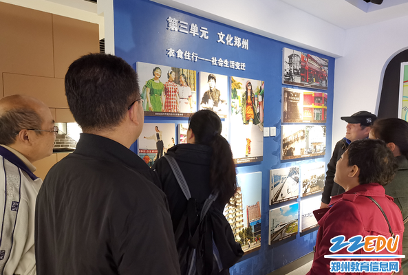 """党员们在""""文化郑州""""展板前回顾畅谈改革开放后郑州的巨大变化"""