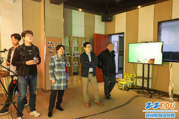 5郑州31·103中校长贾惠芬为范炀教授介绍学校教学平一体化平台与校园电视台开展情况