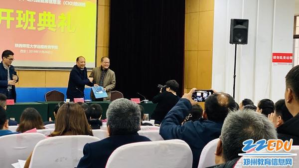 4吴晓昊向陕西师范大学远程教育学院赠送中原区品质教育宣传册和宣传光盘