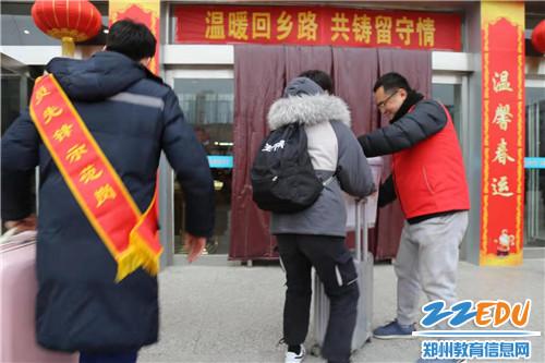 学生处主任郑丹帮旅客拿行李