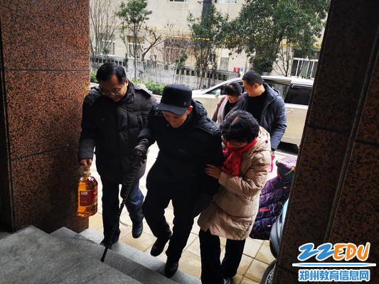 退休教师张荷花(右)扶着98岁的父亲上楼1