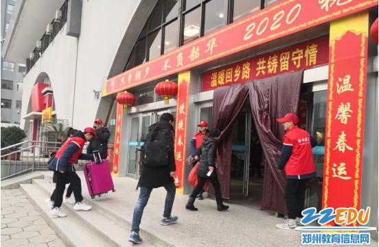 团员志愿者在售票大厅入口处拉开门帘为旅客们提供方便
