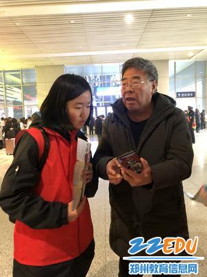 郑州八中志愿者为过往旅客讲解防诈骗知识