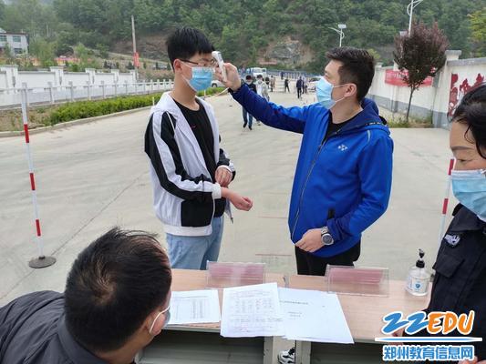 郑州金沙澳门官网4066中许博老师在为返校的学生测量体温