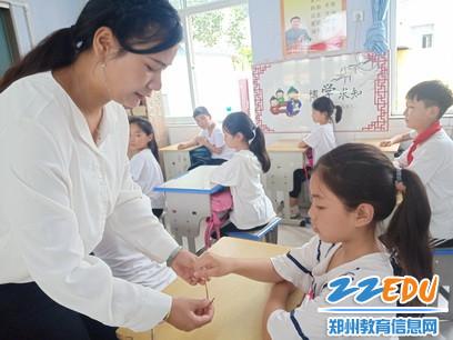 孙庄小学副校长赵婷给学生送五彩绳_调整大小