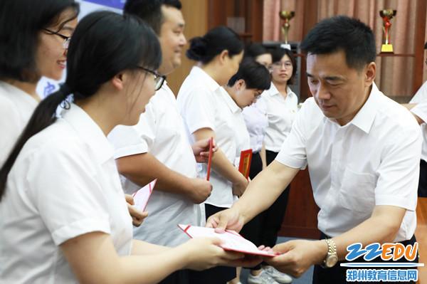 4郭勤学校长为受表彰的通讯员颁发荣誉证书