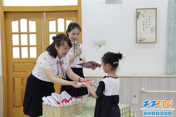 9老师为孩子们颁发毕业证书