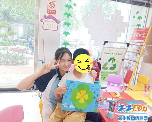 4学生自愿者和孩子们展示手工作品