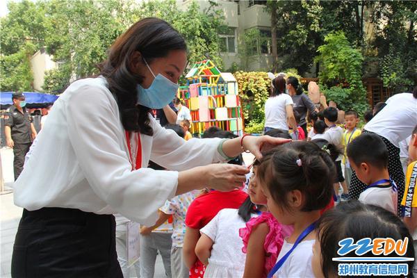 10市實驗幼兒園黨總支書記張莉幫孩子整理發卡