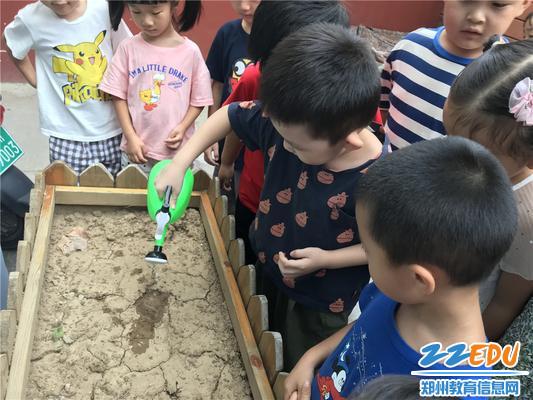 孩子们在花坛边浇水、种植,体验农民伯伯的辛劳
