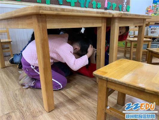 幼儿迅速抱头保护头部躲在结实的桌下