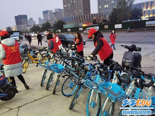 党员老师们摆放学校门口的共享单车