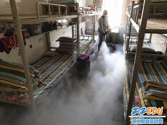 工作人員手持水霧煙霧兩用機對學生宿舍展開消殺
