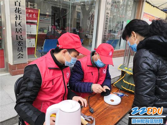 2.志愿者为社区居民修理家电