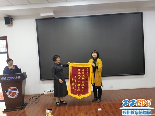 工会主席张恺代表学校接收校友锦旗