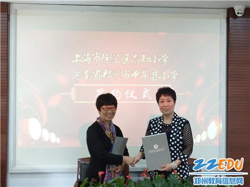 寿圣街小学校长郭芙蓉和求知小学校长陈婕签署协议书。