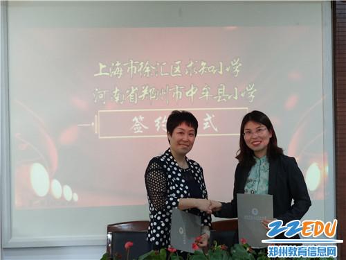 紫薇路小学校长王慧娟和求知小学校长陈婕签署协议书。