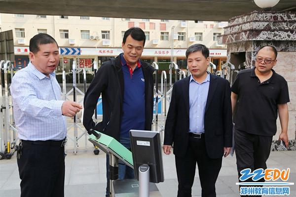 5副校长李伏庆(左一)介绍学生进出校园智能管理系统