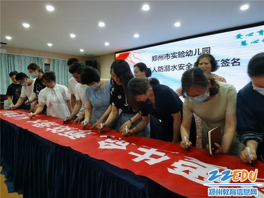 8教职工在防溺水主题条幅上签字