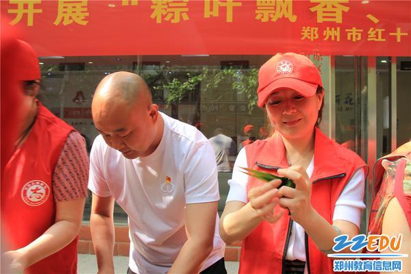 2.市实验幼儿园党总支书记张莉和百花社区党委书记郭新果包粽子