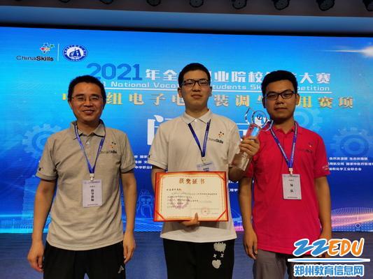 2.郑州市电子信息工程学校参赛选手高海斌(中)与辅导教师李良(左一)、苑锋(右一)