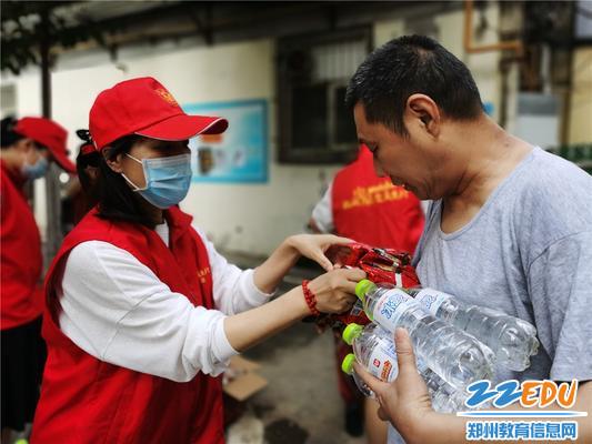 3志愿者向社区居民发放瓶装水